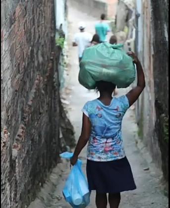 Mulher recebendo doação na comunidade da Várzea
